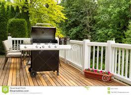 open bbq cooker and bottled beer on outdoor cedar patio stock