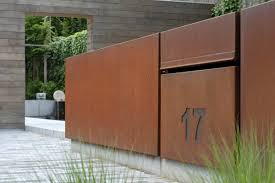 contemporary corten fence contrasts with weathered wood gravel