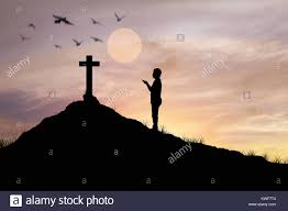 silhouette praying in front of cross with faith and belief stock