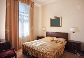 interior of a hotel room for two just a bed near window stock