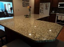 brown wooden kitchen island with white granite countertop plus