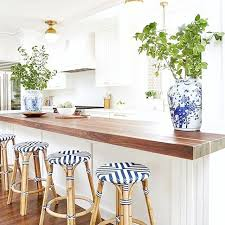 Coastal Kitchen And Bar - white kitchen brass lighting wood accents blue and white ginger