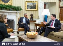 president barack obama receives an update in the oval office from