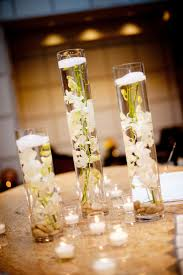 candles on glass with pink flowers laid on white table cloth for