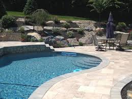 pool with boulder retaining wall backyard landscaping ideas