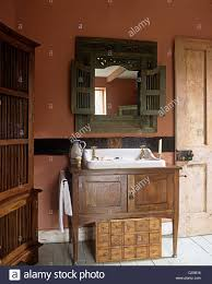 washbasin in wooden cupboard in red country style bathroom stock