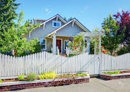grey small cute house with white fence and roses stock photo