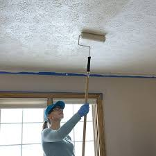 how to paint a textured ceiling woman rolling paint onto the ceiling textured paint over ceiling
