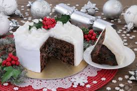 christmas cake and slice with holly bauble decorations and winter