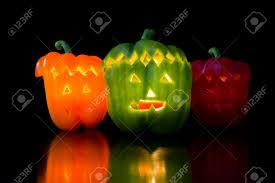 halloween stock background scary faces carved on bell peppers on a dark background for