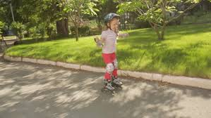 learns to roller skate in the park stock footage