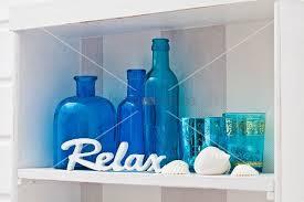 blue ornamental bottles and glasses on white shelf bild kaufen