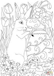 easter rabbit is decorating an egg coloring page free printable