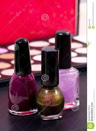 three different nail polish colors and a make up background pink