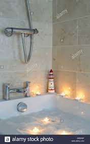 bathroom showing bath fitted with chrome bath and shower taps stock photo bathroom showing bath fitted with chrome bath and shower taps filled with relaxing bubble bath and lit floating candles in bath
