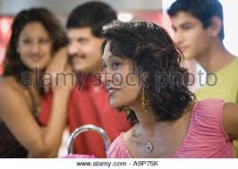 indian teenage boy with family in kitchen preparing food stock