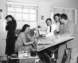 The Drafting Table Staff Of The Aid Unit Meeting Around A Drafting Table At