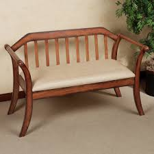 brown wooden bench with four curving legs also bars on the back