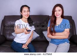 best sofa for watching tv two best friends watching tv with remote on sofa in living room at
