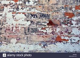 old layers of colorful peeling paint on exterior brick wall of a