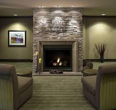 interior stacked stones fireplace displaying with grey fabric