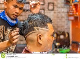 barber haircut a customer at barbershop editorial stock photo