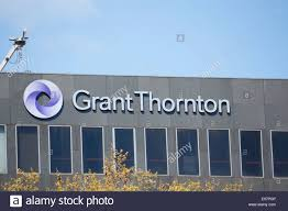 grant thornton logo and company name on top of skyscraper office