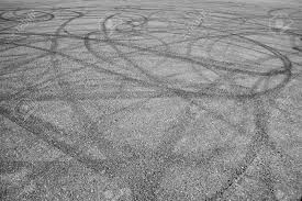 a bunch of random skid marks from cars in an empty asphalt parking