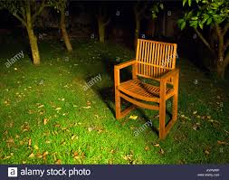 Background With Chair Wooden Chair In The Garden At Night On A Grass Lawn With Trees In