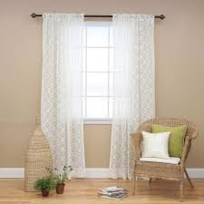 house with neutral wall colors and rattan chair also lace curtains
