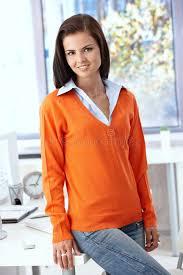 le de bureau orange joli employé de bureau souriant dans le pull orange image stock