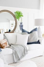 white slipcovered sofa large mirror living room all white