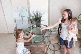 Setting The Table by A Mother And Daughter Setting The Table Together Stock Photo