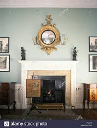antique girandole mirror above fireplace with an antique fire
