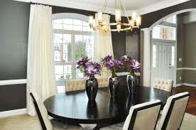 black wooden dining table with white chairs also chandelier also