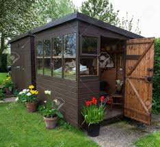garden shed exterior in spring with door open tools flowers