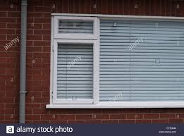 white framed window with closed white venetian blind in red brick