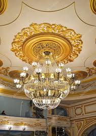 crystal chandelier and gilded stucco moldings on the ceiling of