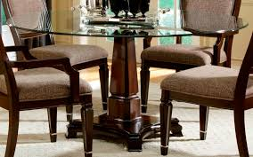 single brown wooden leg with round glass dining table top combined