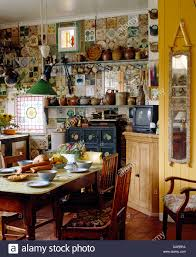 old pine table and chairs in cluttered cottage kitchen with narrow