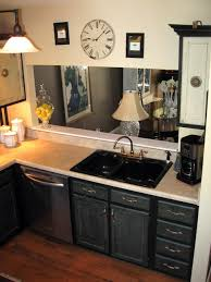 an ebony sink stands out against the cream counters in this