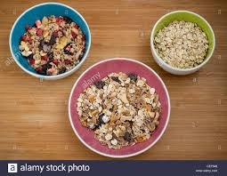 a pink bowl of muesli with dried fruit blue bowl of fruit cereal