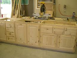 glass countertops unfinished wood kitchen cabinets lighting