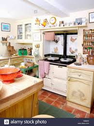 white aga oven and terracotta tiled floor in cottage kitchen with