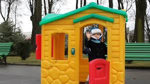 cute kid playing in a colored little house in the park say