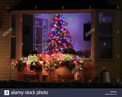 New Year Outdoor Decoration by Window With Decorated Glowing Christmas Tree Inside A House And