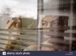 sad woman looking through blinds on window stock photo royalty