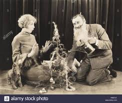 woman watching man in fake beard watering christmas tree stock