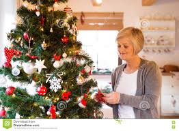 Home Decorating Christmas by Senior Woman At Home Decorating Christmas Tree Stock Photo