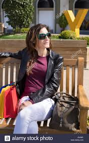 brown hair woman with white jeans red shirt leather blazer